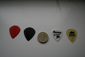 My current crop: Jim Dunlop Jazz 3 XL, another Jimp Dunlop Jazz 3 XL (thicker guage, hence the black), a £1 coin (for measurement), a Paul Gilbert Ibanez signature plectrum and a Dunlop Ultex Sharp)